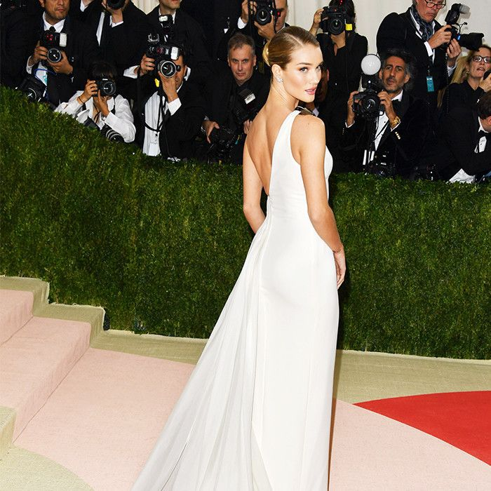 Rosie Huntington-Whitely on the red carpet wearing a long, white dress