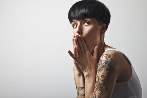 Woman with short black hair and a tattoo on her shoulder