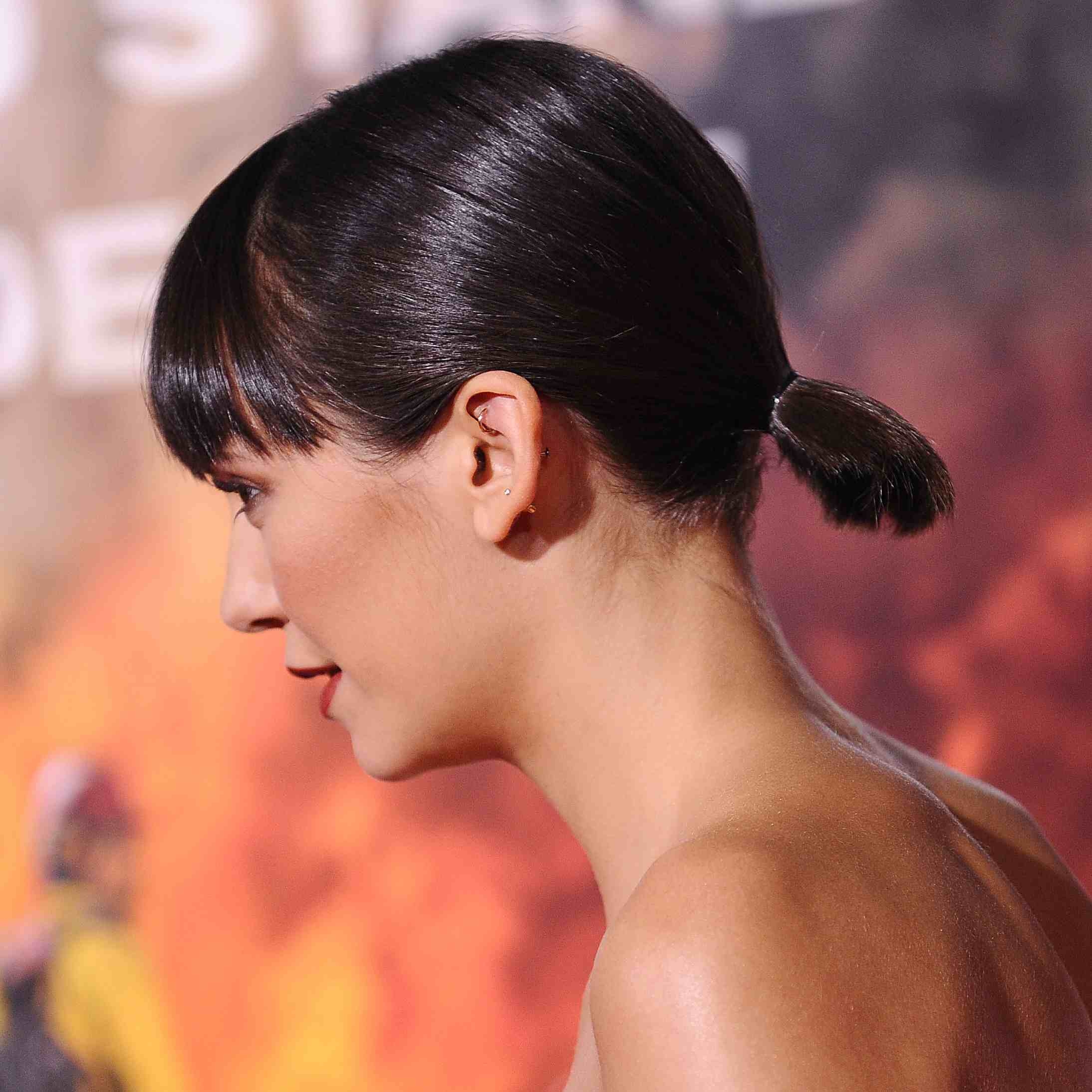 Nina Dobrev with a short, low ponytail