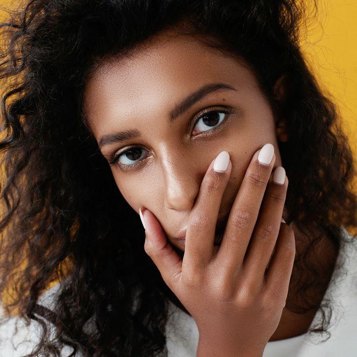 best spot cream: Woman touching her face