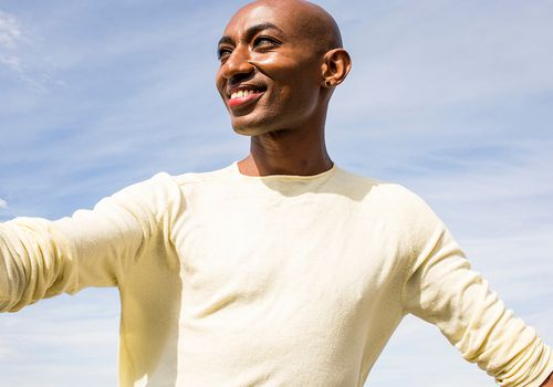 Person wearing yellow shirt with sky background