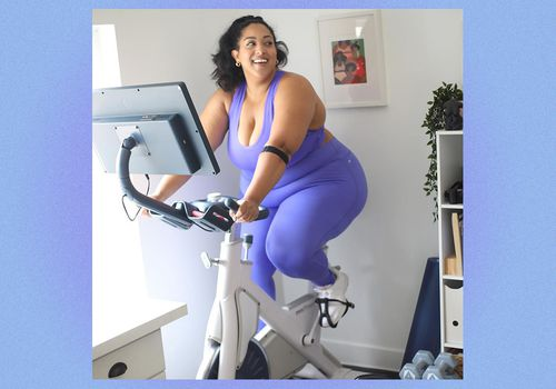 Woman in fitness clothing smiles on a stationary bike.