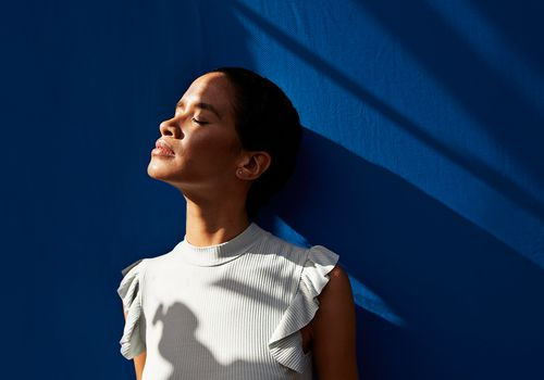 Woman against blue wall