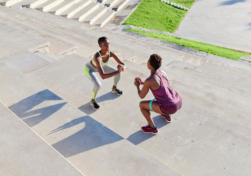 Two women perform squats outdoors.