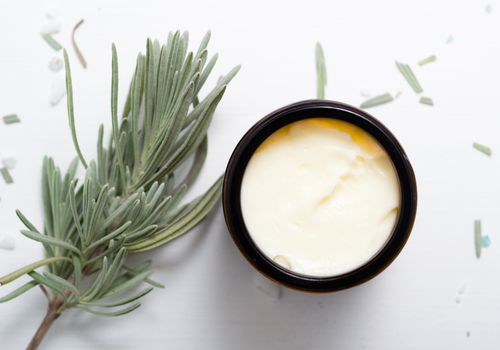 Shea butter in brown glass pot with lavender leaves