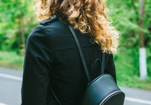 Woman with thick hair and a mini backpack