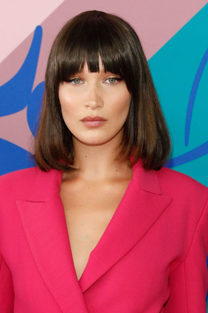 Bella Hadid with bangs in a pink blazer.