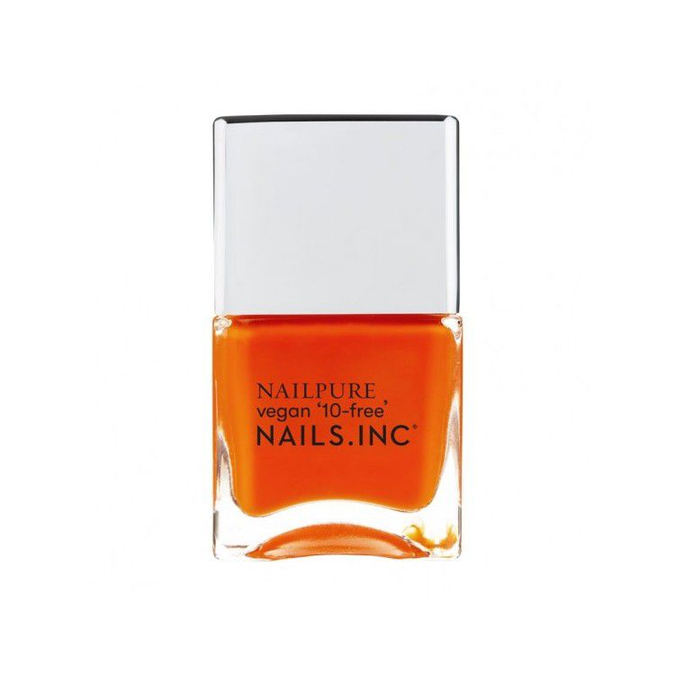 Bright orange nail polish on a white background.