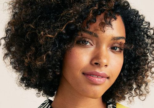 woman with curly brown hair and natural makeup