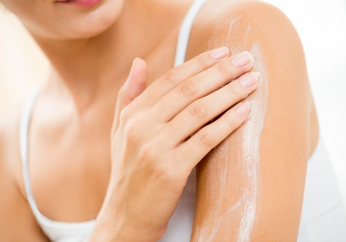 Person applying lotion to back of arm.