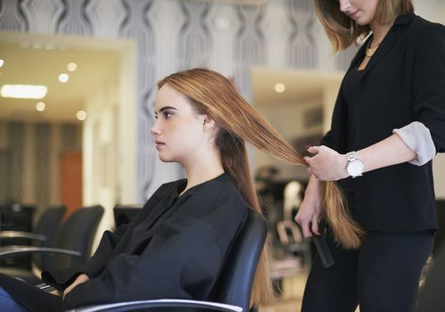 Woman getting long hair cut