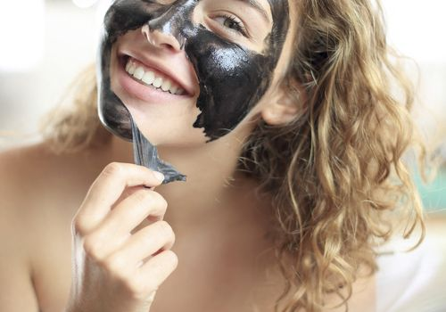 smiling woman peeling off charcoal face mask