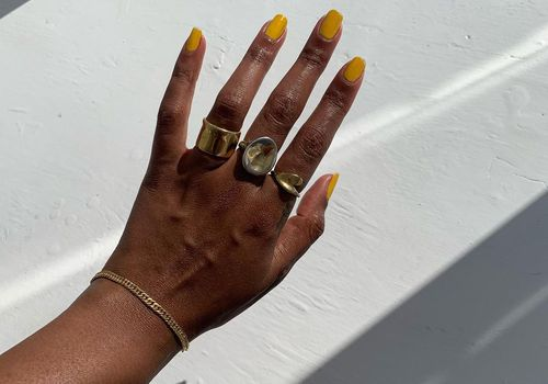 hand with yellow squoval nails and gold rings