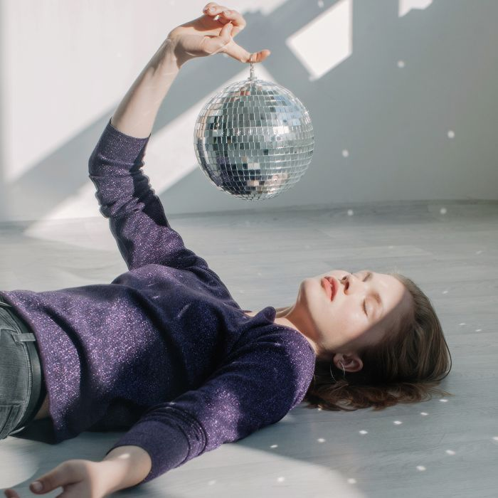 Glass Skin: Woman with glowing skin holding a disco ball