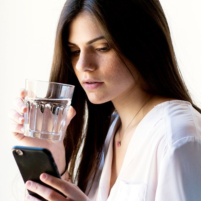 Woman holding a glass of water and looking at her cellphone
