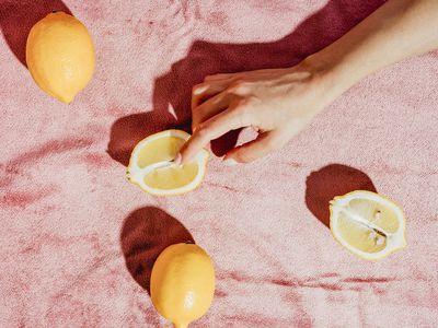 woman holding lemon against pink background