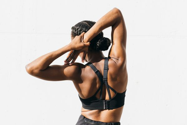 woman stretching arms against white background