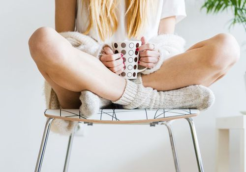 girl with socks holding a mug