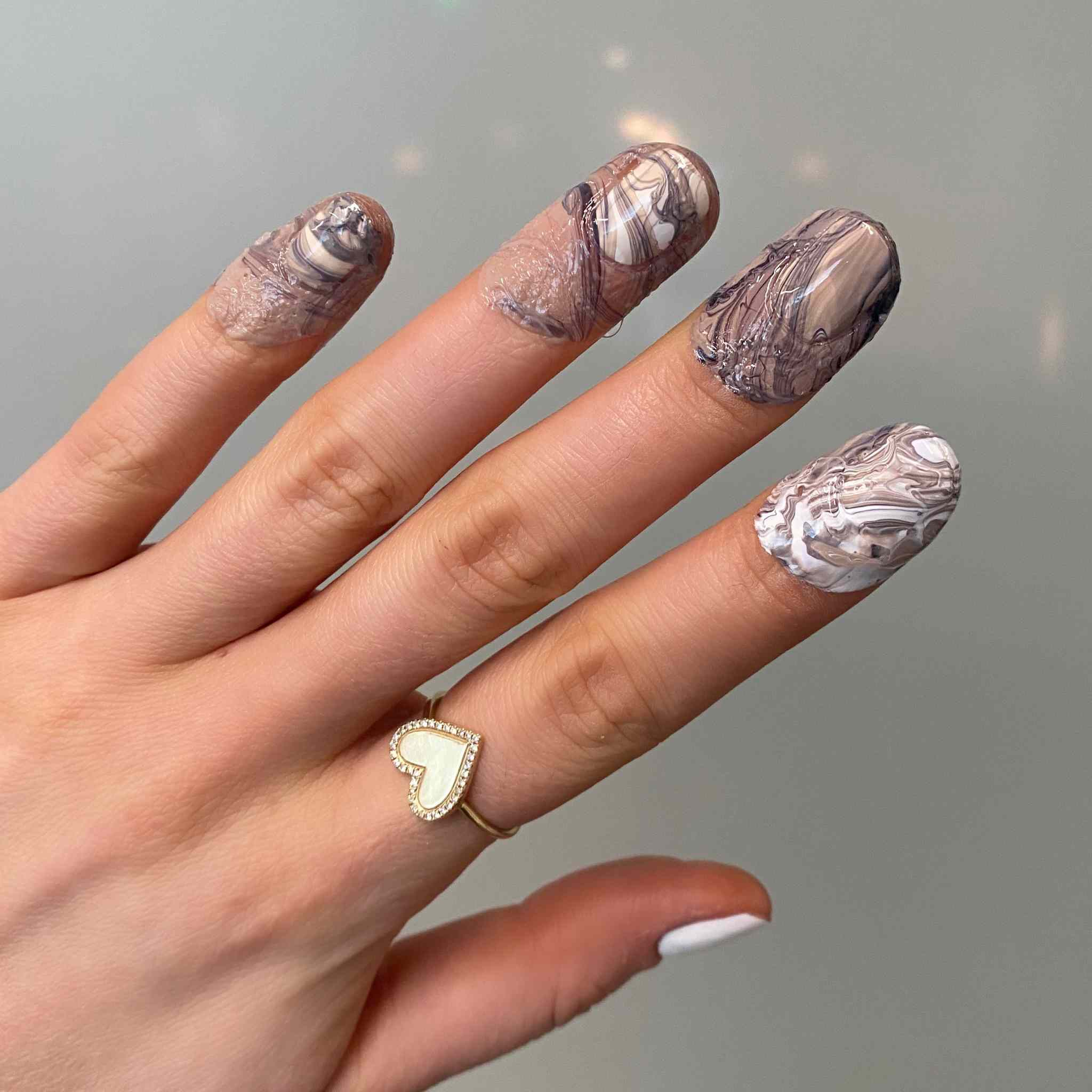 Fingers covered in nail polish.