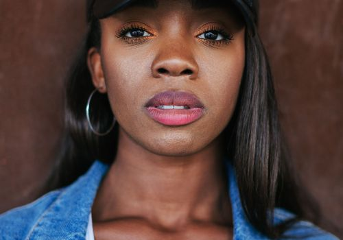 a woman with relaxed hair wearing a baseball hat and denim jacket