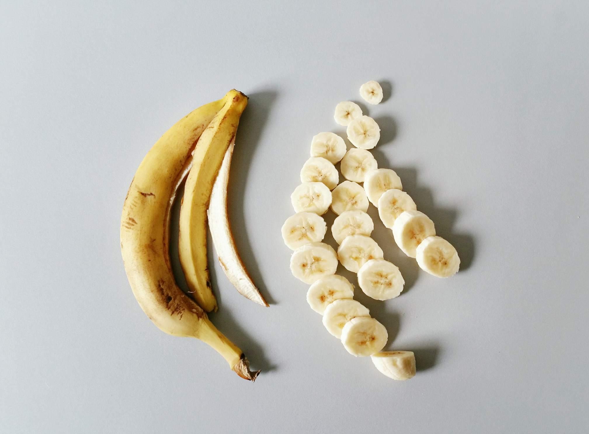 A banana peel laying next to sliced banana
