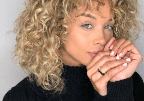 woman with curly blonde hair with lowlights