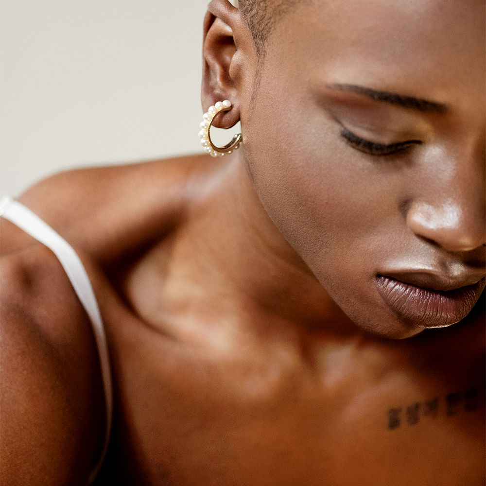 closeup of black femme with earring and collar bone tattoo