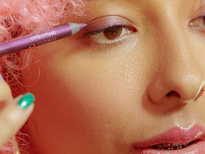 girl putting on eyeliner in pink aesthetic