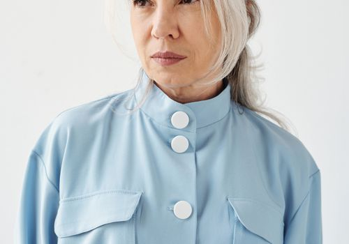 Woman with white hair wearing a blue shirt