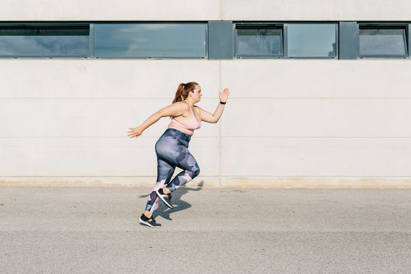 woman sprinting outdoors in an industrial setting