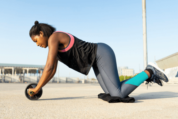 woman using ab roller to workout