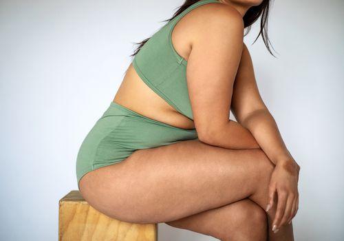 Woman sitting on a wooden block, legs crossed