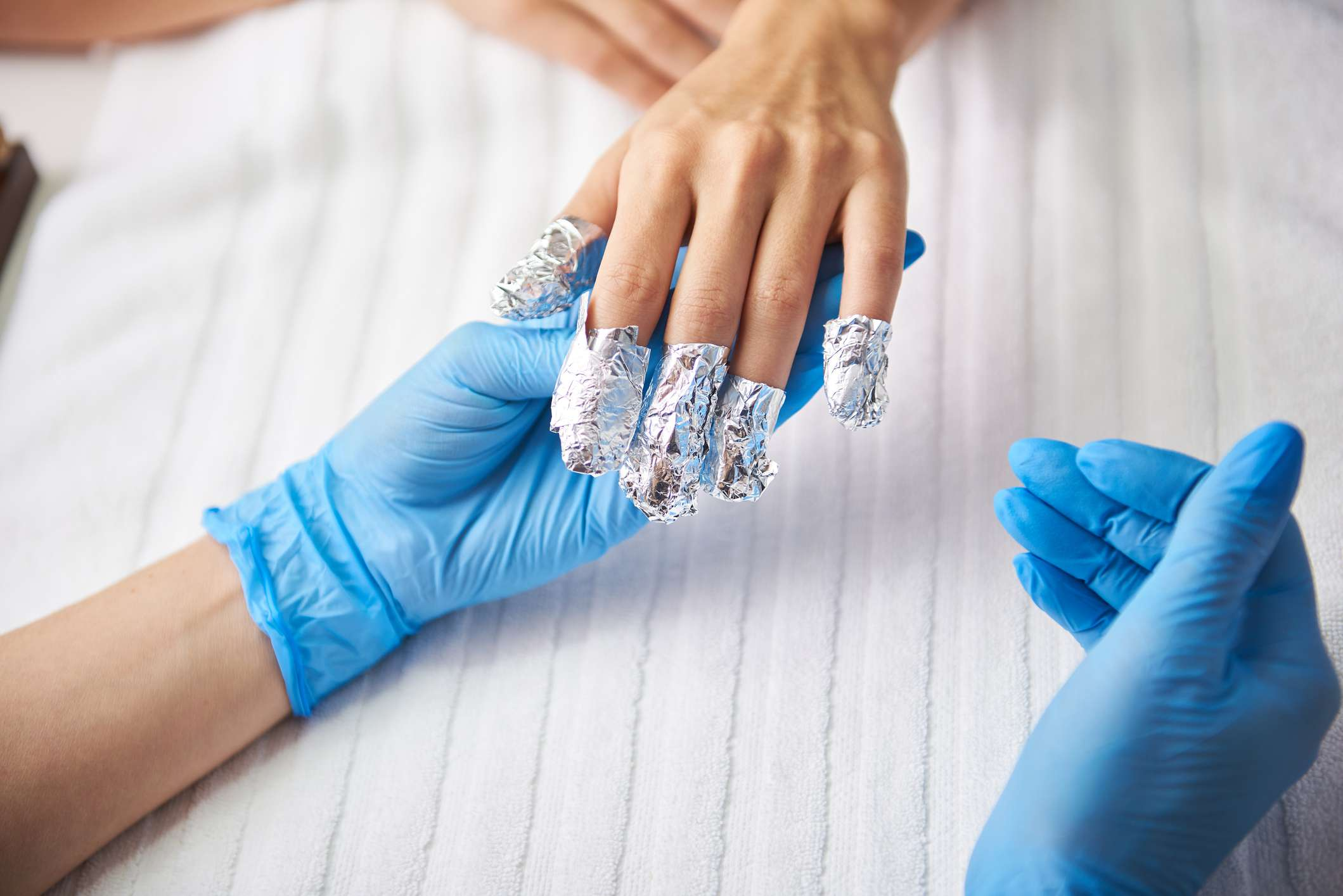 Person getting gel nail polish removed.
