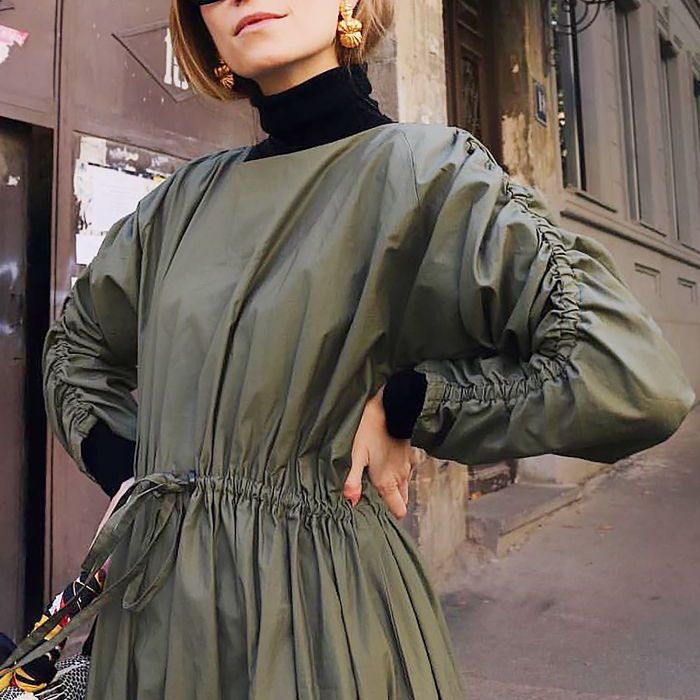Young woman wears black turtleneck beneath an olive green, long-sleeved dress