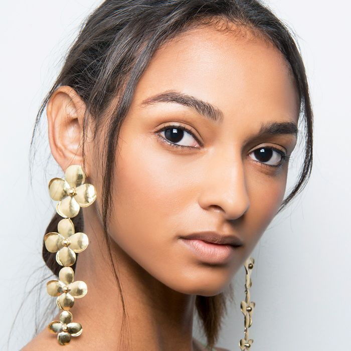 Young looking model with long gold flower earrings