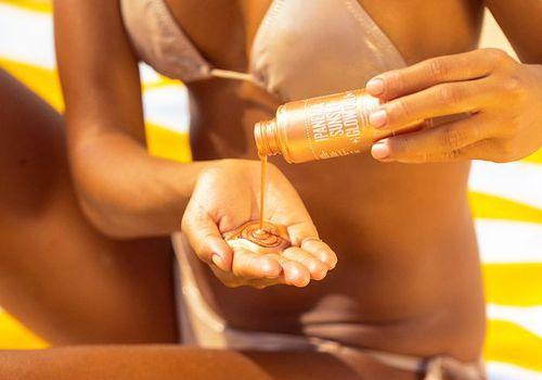 woman applying sol de janeiro glow oil