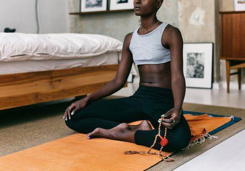 Woman sitting on a yoga mat, holding a mala as she meditates.