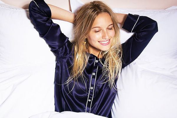 Woman smiling while lounging in bed