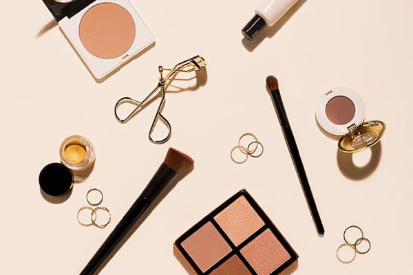 Multiple beauty products and gold rings spread out on a light peach background