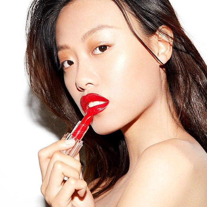 Woman applying red lipstick to her lips