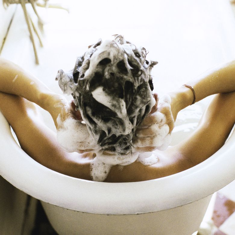 Woman in bath shampooing hair