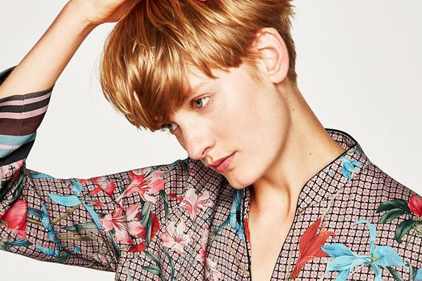 Woman with short blonde hair wearing a floral satin blouse