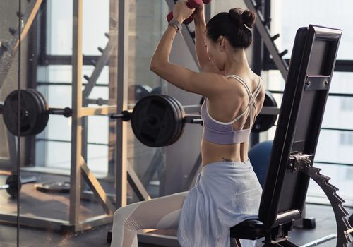 Woman lifting weights at gym bad form