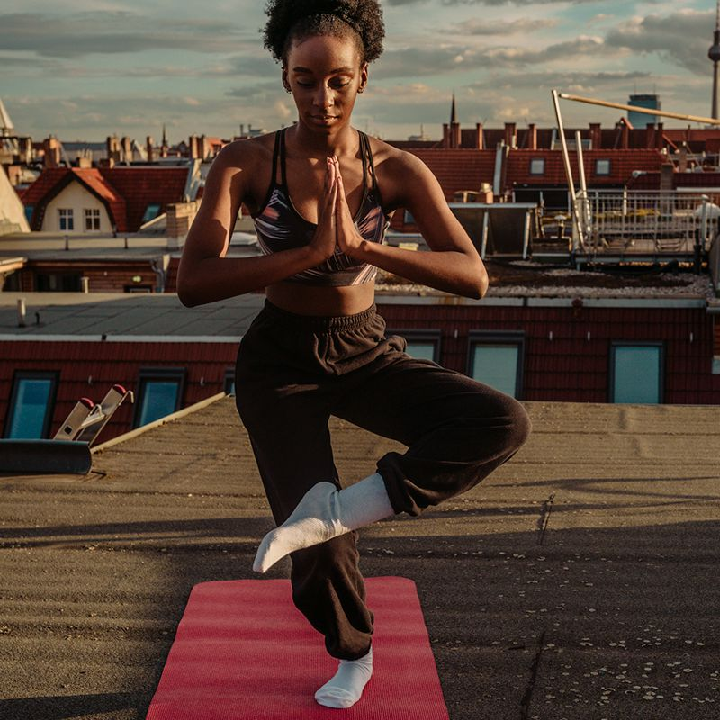 person doing yoga on rooftop