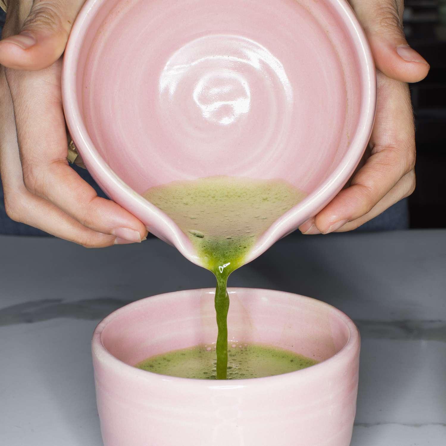 hands pouring green tea into a pink mug