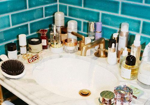 Beauty products spread out on bathroom sink.