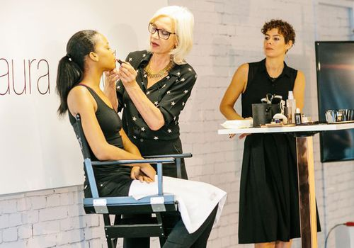 Mary Greenwell applying makeup to a model's face at the Laura Mercier Flawless Face workshop