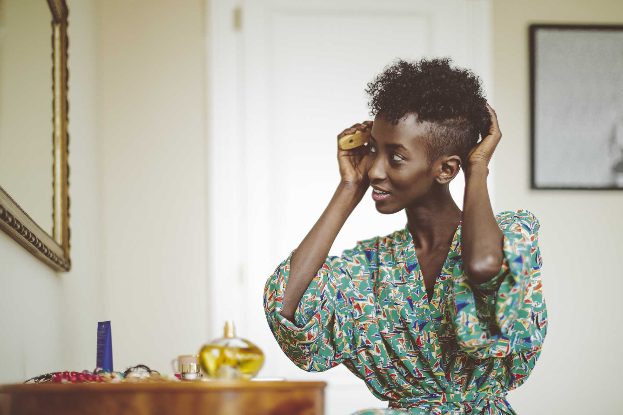Woman combing hair while looking in mirror