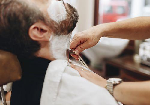 Man having his beard shaved