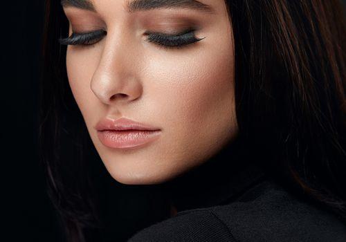 Model looking down against black background